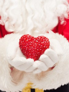 christmas, holidays, love, charity and people concept - close up of santa claus with heart shape decoration over lights background